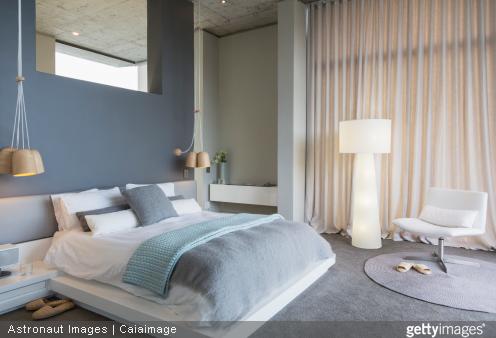 Des voilages sur mesure et un éclairage indirect permettent de donner un style design à votre chambre.